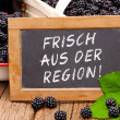 Постер, плакат: Slate blackboard with the Germans words: Frisch aus der Region