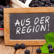 Постер, плакат: Slate blackboard with the Germans words: Aus der Region