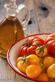 Tomatoes in a bowl and olive oil — Stock Photo