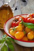 Tomatoes in a bowl, basil and olive oil — Stock Photo