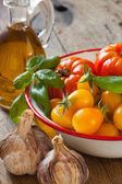 Tomatoes in a bowl, garlic, basil and olive oil — Stock Photo