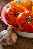 Tomatoes in a bowl and garlic — Stock Photo
