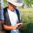 Cowboy leans on hay with tablet computer — Stock Photo #22391007