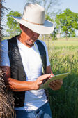 Cowboy leans on hay with tablet computer — Стоковое фото