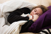 Sick young woman sleeps on couch — Stok fotoğraf