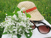 Bouquet of lily of the valley flowers sunglasses and hat — Stock Photo