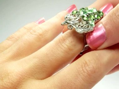 Jewelery ring with green emerald crystals putting on the finger — Vídeo Stock
