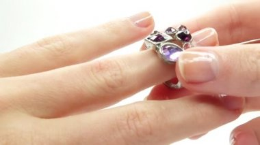 Jewelery ring with purple crystals putting on the finger — Video Stock