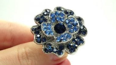 Jewelery ring with blue sapphire crystals putting on the finger — Video Stock