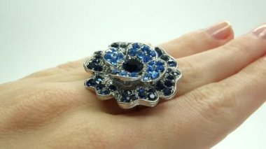 Jewelery ring with blue sapphire crystals putting on the finger — Wideo stockowe