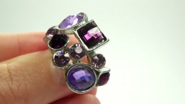 Jewelery ring with purple crystals putting on the finger — Stock Video