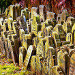 Old grave stones piled up against a wall, — Stockfoto