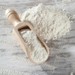 Heap of plain flour with wooden scoop — Stock fotografie