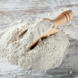 Heap of plain flour with wooden scoop — Stockfoto