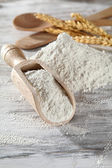 Heap of plain flour with wooden scoop — Stock Photo