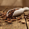 Wooden scoop with roasted coffee beans — Stock Photo