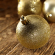 Gold baubles on rustic table — Stok fotoğraf