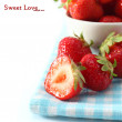 Strawberries in a bowl and on a sheet on a white background — Stock Photo