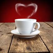 Tasse kaffee auf einem holztisch mit dampf als ein zeichen der liebe — Stockfoto