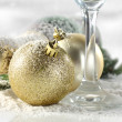 Photo of champagne and gold balls on snow — Stock Photo