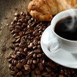 Aromatic coffee with croissant on coffee beans — Stock Photo #18532561