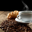Aromatic coffee with croissant on coffee beans — Stock Photo
