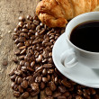 Aromatic coffee with croissant on coffee beans — Foto Stock