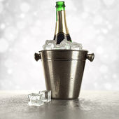 Champagne in ice on silver background — Stock Photo