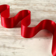 Red ribbon on a wooden table — Stock Photo #18680427