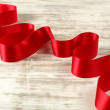 Red ribbon on a wooden table — Stock Photo