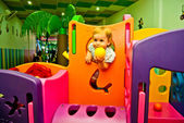 Girl 1,5 years old with yellow ball in hand has fun in game complex — Stock Photo