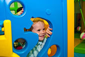 Girl 1,5 years old peeps out through the holes of game complex — Stock Photo