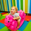 Girl 1,5 year old swinging on a pink rocking horse - Stock Photo
