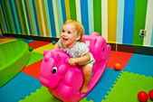 Girl 1,5 year old swinging on a pink rocking horse — Stock Photo