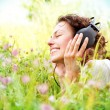 Beautiful Young Woman with Headphones Outdoors. Enjoying Music - Stock Photo
