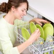 Dishwasher. Young woman in the Kitchen doing Housework. Wash-up - Zdjęcie stockowe