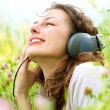Beautiful Young Woman with Headphones Outdoors. Enjoy Music - Stock Photo