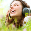 Stock Photo: Beautiful Young Woman with Headphones Outdoors. Enjoy Music