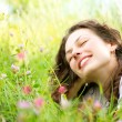 Beautiful Young Woman lying in Meadow of Flowers. Enjoy Nature — Stock Photo #12800879