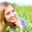 Beautiful Girl lying on Meadow of Flowers and Green Grass — Stock Photo #12801238