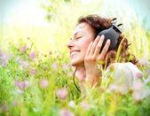 Mooie jonge vrouw met hoofdtelefoon buitenshuis. genieten van muziek — Stockfoto
