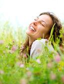 Vacker ung kvinna liggande på äng med blommor. njuta av naturen — Stockfoto