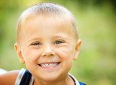 Kleiner junge lachend. kind über natur grün hintergrund — Stockfoto