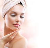 Spa meisje. mooie jonge vrouw na bad aanraken haar gezicht — Stockfoto
