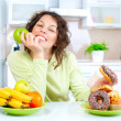 Diet. Beautiful Young Woman choosing between Fruits and Sweets - Stockfoto