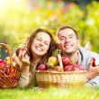 Couple Relaxing on the Grass and Eating Apples in Autumn Garden — Stockfoto