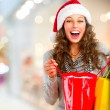 Christmas Shopping. Happy Woman with Bags in Mall. Sales - Stock Photo