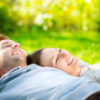 Park. Young Couple Lying on Grass Outdoor — Stock Photo