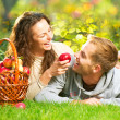 Couple Relaxing on the Grass and Eating Apples in Autumn Garden — Stockfoto #14134358
