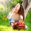 Happy Smiling Young Woman Eating Organic Apple in the Orchard - Stock Photo